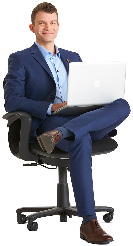 Businessman sitting on desk chair with mac laptop resting on his legs